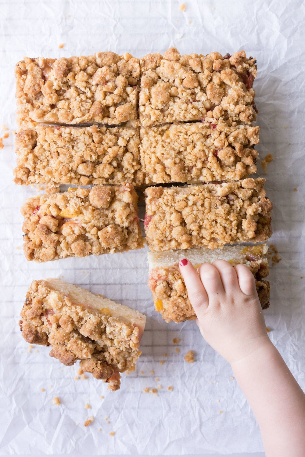 Peach and rhubarb crumb cake with brown butter streusel. This soft vanilla bean cake is covered with chopped fruit, and finished with a toasty, crunchy brown butter streusel.