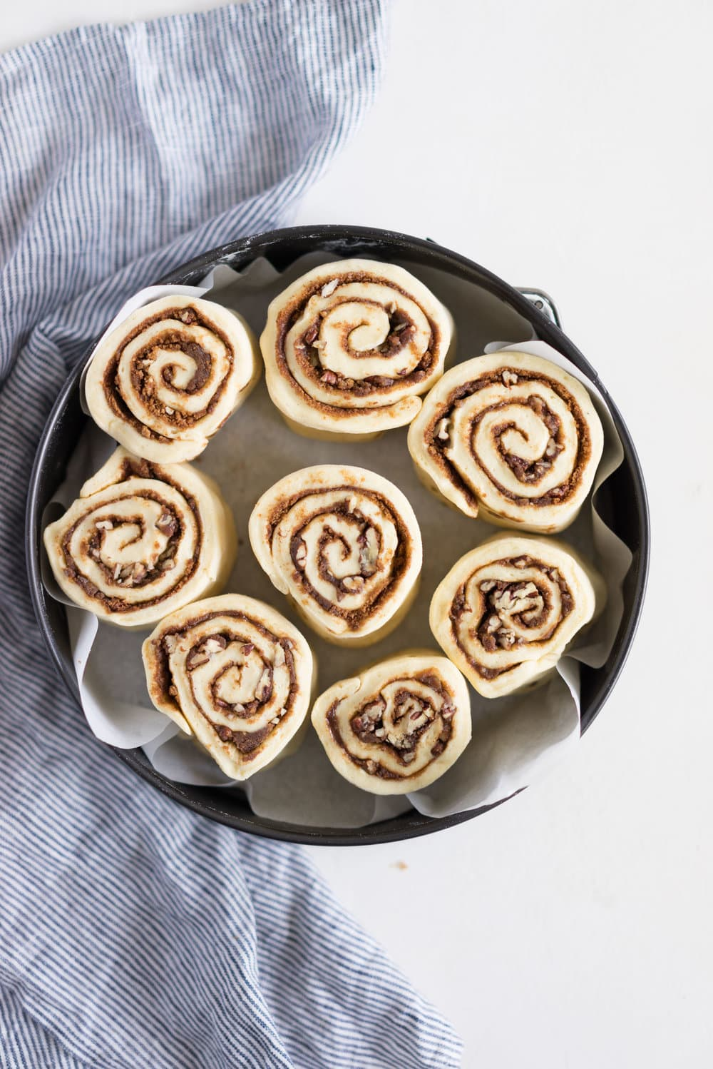 Overnight Cinnamon Buns with Cream Cheese Frosting - Pillowy brioche that is prepared the night before, then rolled out the next morning, stuffed with cinnamon sugar and toasted peanuts, then smothered in cream cheese frosting while still warm. The perfect treat to please a crowd. #cinnamonrolls #overnight #brioche