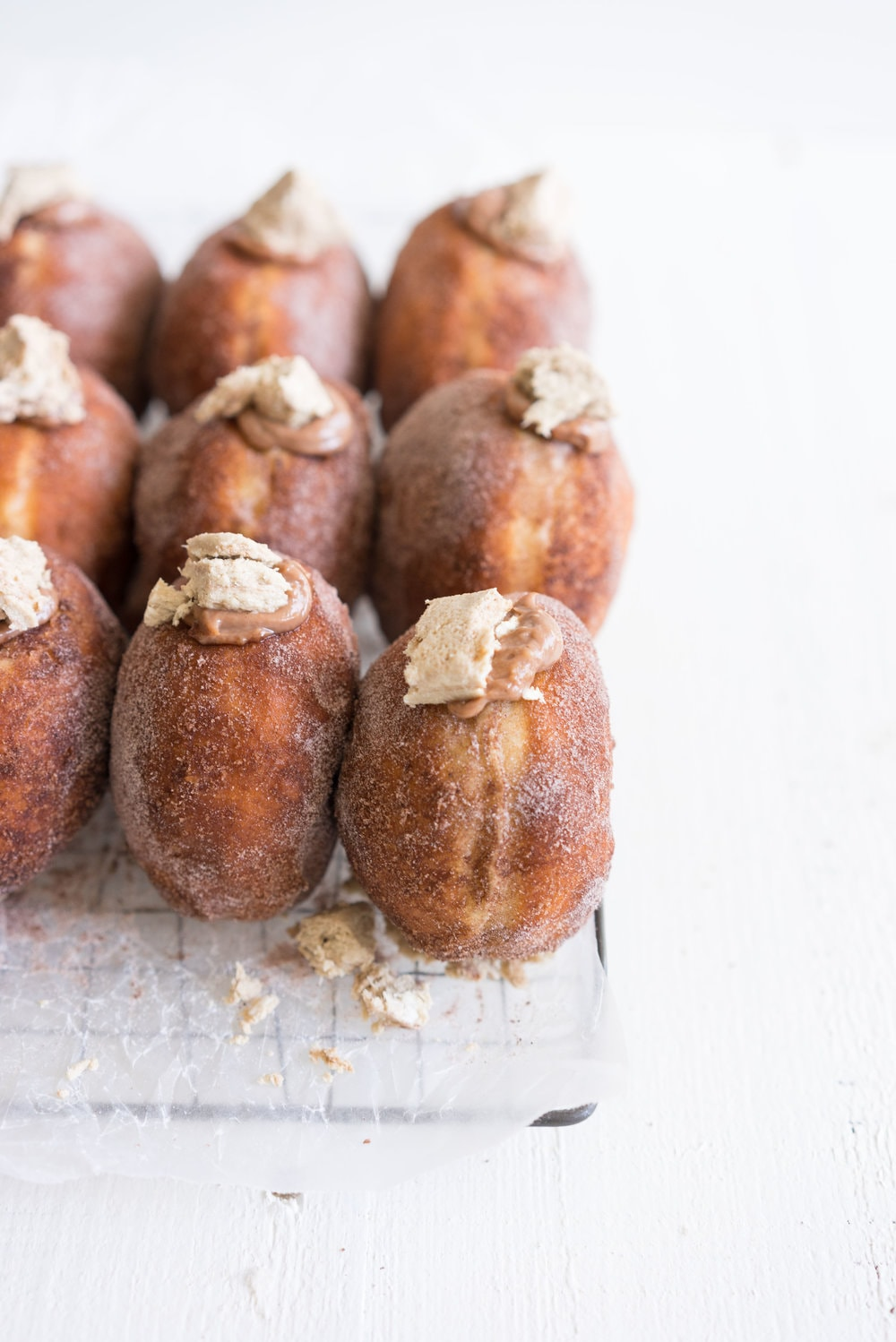 Brioche doughnuts filled with chocolate tahini pastry cream and topped with Halva