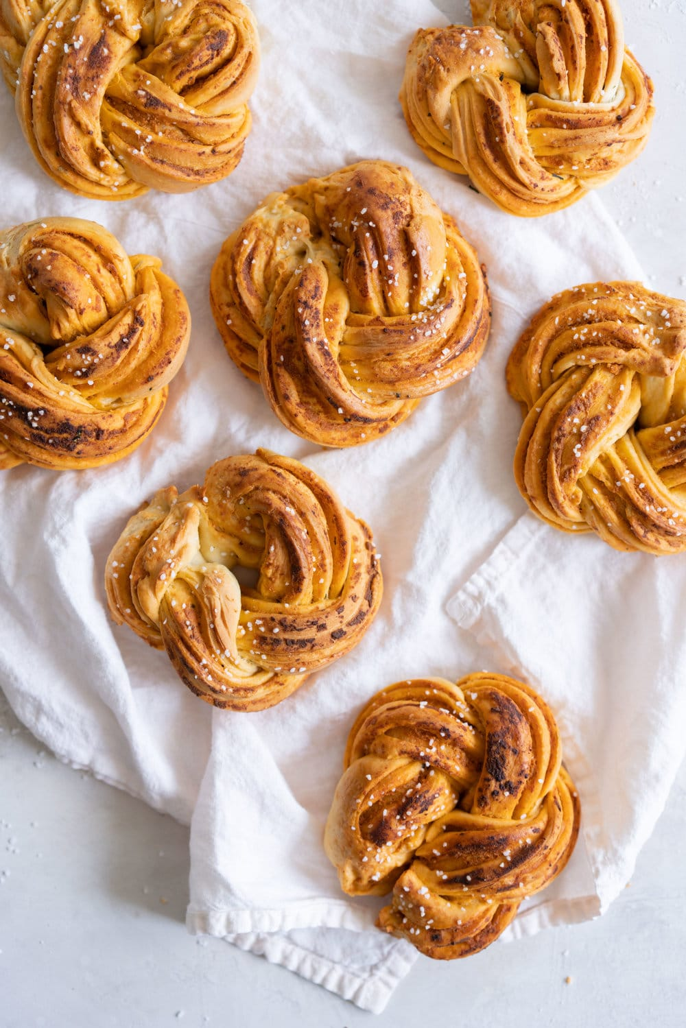 Fluffy Brioche knots filled with Roasted Garlic, Tomato and Ricotta Pesto. Rolled up and twisted into knots, and baked to golden, puffy perfection. Perfect on their own or as an addition to a lunch or alongside a bowl of soup. #brioche #briocheknot #pestobrioche