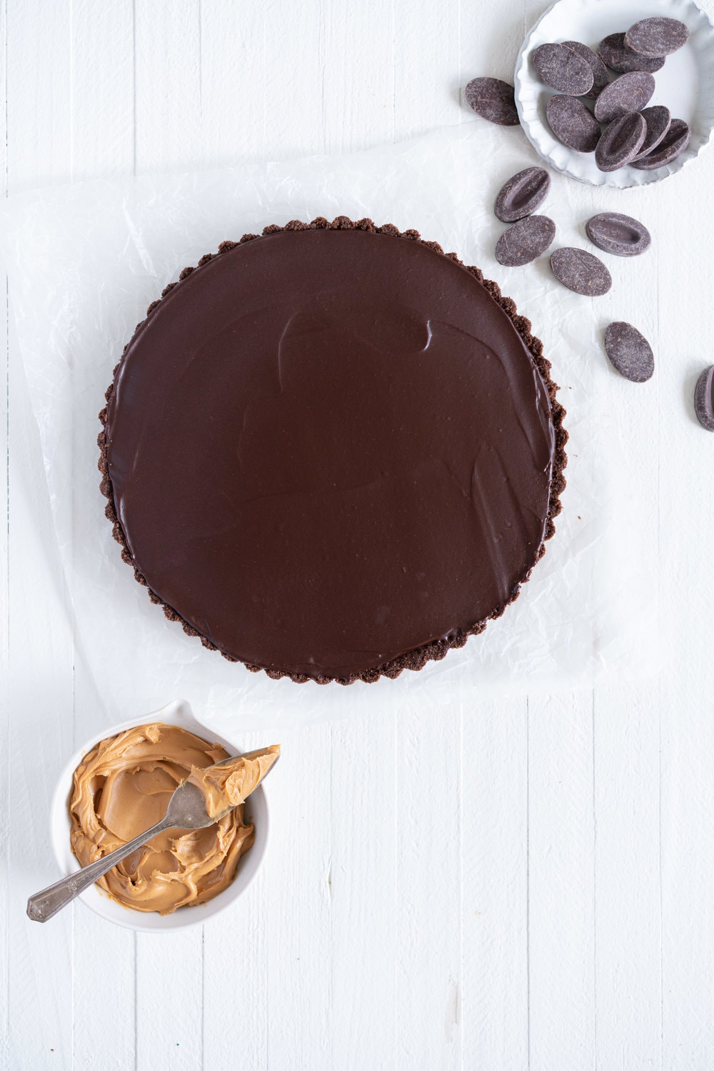 Dark Chocolate Peanut Butter Tart with Peanut Butter Whipped Cream - a chocolate graham cracker crust is topped with a silky dark chocolate peanut butter filling and finished with a creamy peanut butter whipped cream. Everyone needs a recipe like this up their sleeve to wow their friends. Easy to make ahead, and always a crowd pleaser. #chocolatetart #peanutbuttertart #chocolate #peanutbutter