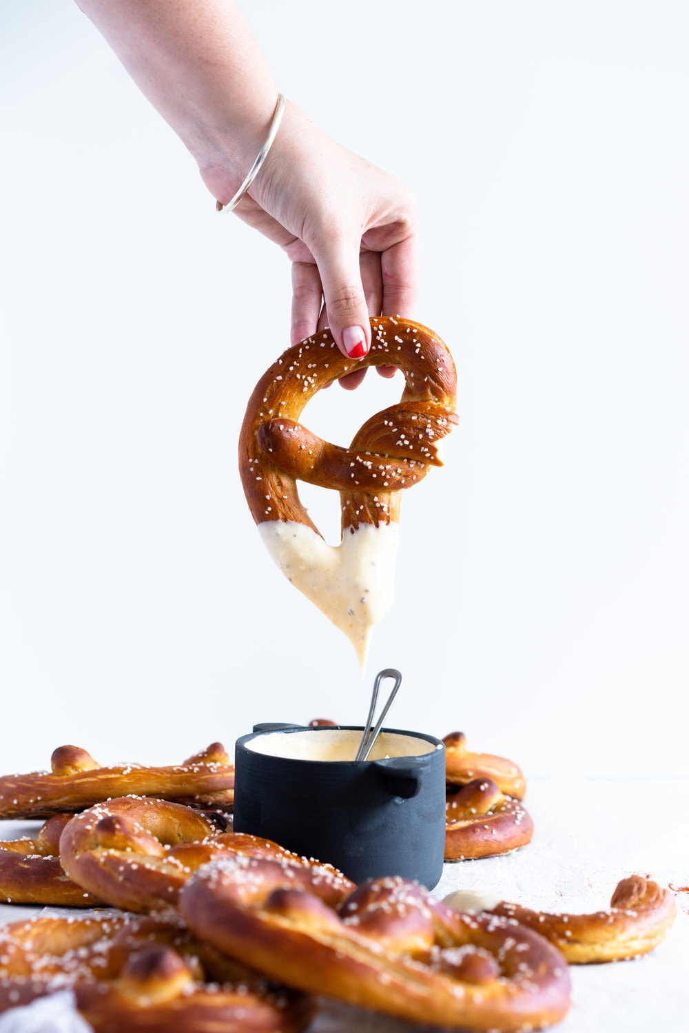 Authentic pretzels, baked until perfectly soft and golden brown, dipped in a super easy cheesy mustard dipping sauce that comes together extremely quickly. The perfect snack for a crowd. #pretzels #cheesesauce #cheesedip #americancheese #bread #homemadepretzels #bakingsodadip