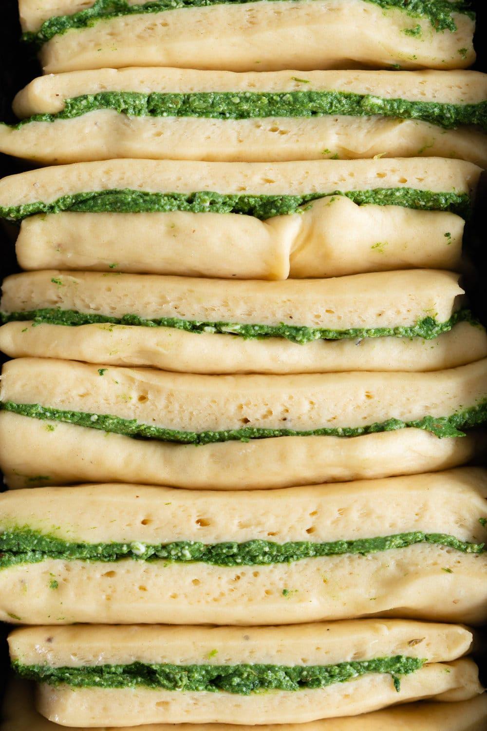 Spinach, Feta and Basil pesto Pull-apart bread. This pull apart loaf is super easy to put together, while being very impressive at the same time! A simple dough is filled with a spinach, feta and basil pesto filling, then cut into rectangles and layered into a loaf tin for the perfect pull apart bread. #pullapartbread #basilpestobread #spinachloaf