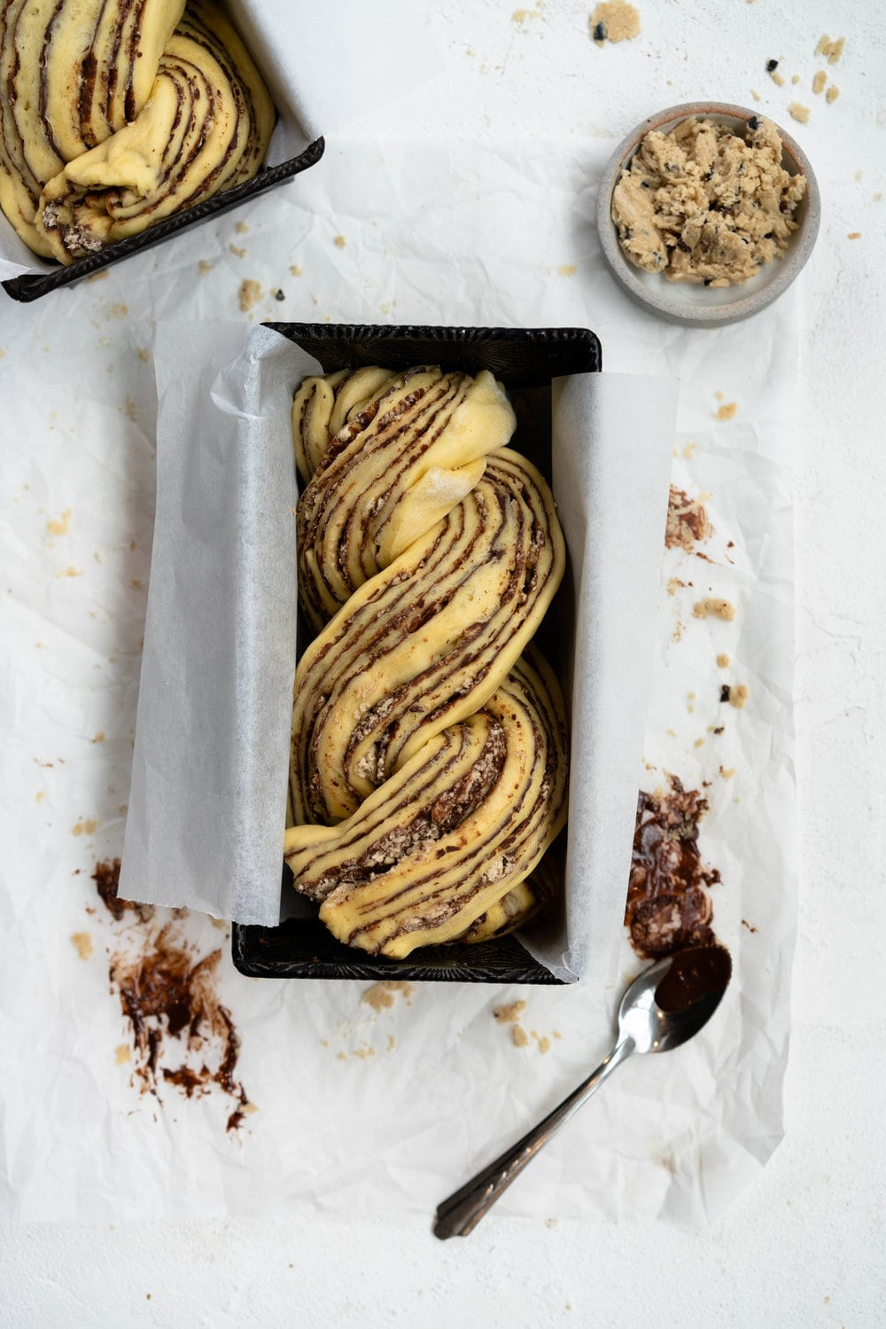 Dark Chocolate, Tahini, and Halva Brioche Babka. Fluffy brioche dough is spread with a dark chocolate tahini filling and sprinkled with halva, then rolled up and turned into the most perfect twisty bread. Perfect for a delicious breakfast or a snack with a coffee. #babka #brioche #tahini #halva
