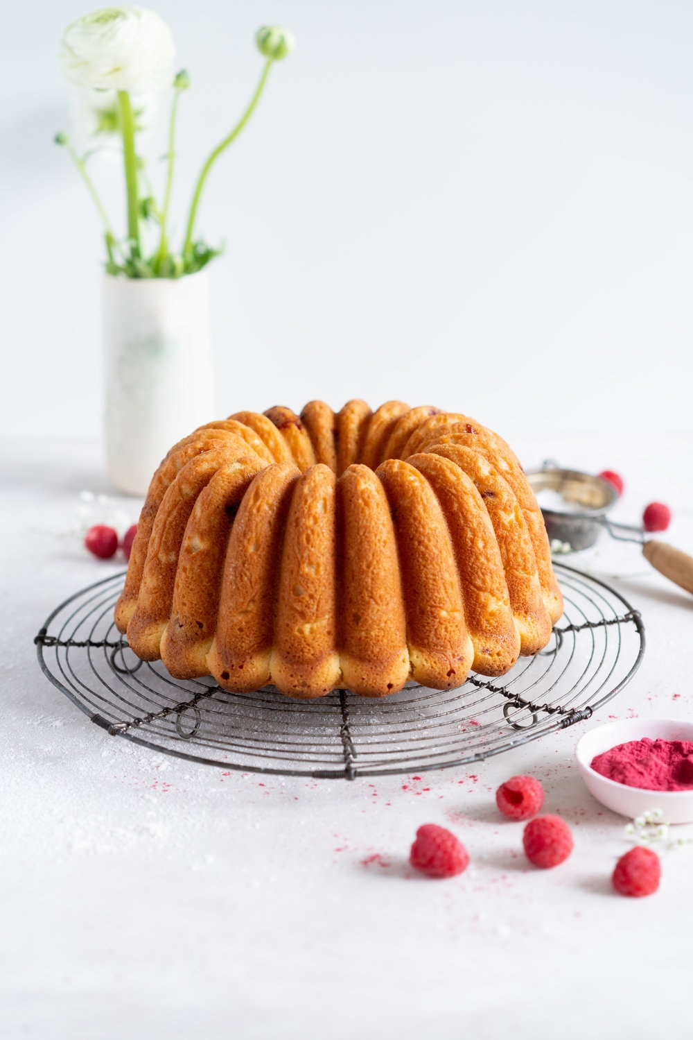 Raspberry Ricotta bundt cake - a tender vanilla bean bundt cake is accented with tart raspberries. This easy, stir together cake is the perfect texture, is simple to put together, and is perfect for feeding a crowd. #bundtcake #ricottacake #raspberrybundt