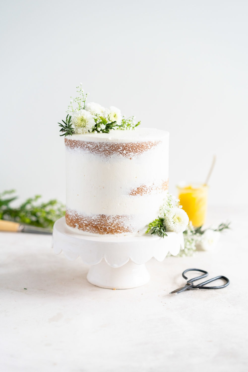 Olive Oil Layer Cake with Meyer Lemon Curd and Rosemary German Buttercream. Fruity olive oil cake is filled with a zesty meyer lemon curd, and finished in a semi naked style with a rosemary german buttercream and spring flowers. #nakedcake #oliveoilcake #meyerlemon