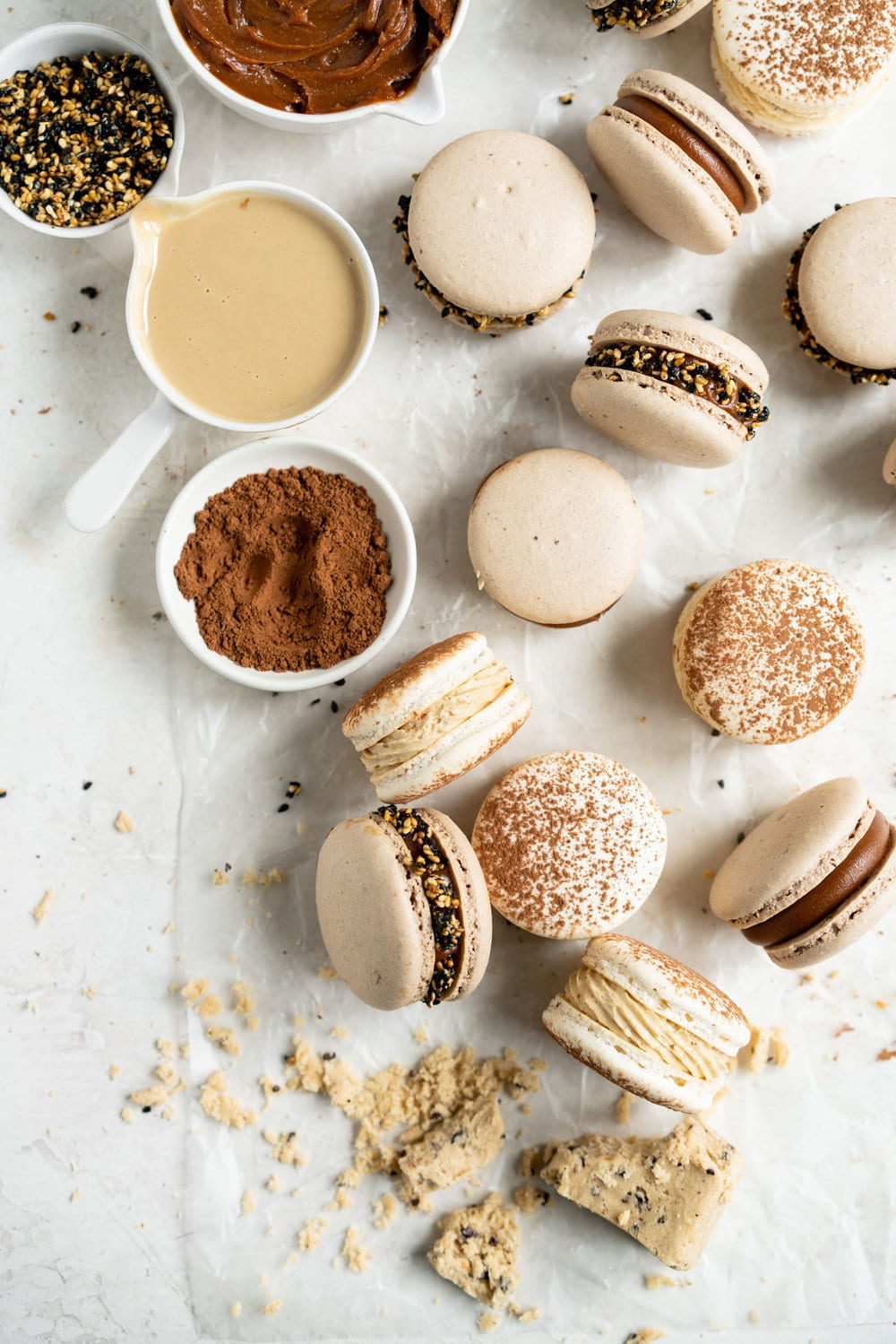 Sesame Macarons Two Ways - Chocolate Macarons with Salted Caramel Tahini Milk Chocolate Ganache and Sesame Brittle, and Vanilla Bean Macarons with Coffee German Buttercream and Halva. These two 'variations on a theme' show off the amazing versatility of tahini - a silky tahini chocolate ganache, and a halva stuffed macaron. #frenchmacarons #glutenfree #macarons