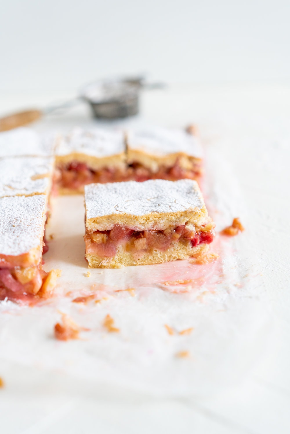 Rhubarb Shortcake Bars - Two layers of sweet, short pastry enclose a jammy, rhubarb centre. These rhubarb shortcake bars differ from traditional American shortcake in that they are all baked together, giving you a range in texture - crisp pastry, soft where it hits the tart rhubarb centre, and a dusting of powdered sugar to finish. This recipe is amazingly versatile and works great with any stone fruit or berries. #rhubarb #rhubarbshortcake #shortcake #newzealandshortcake
