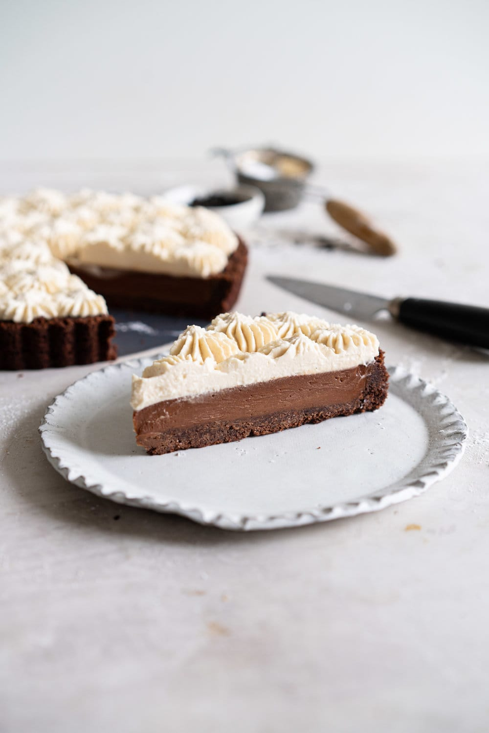 Dark Chocolate Salted Caramel Ganache Tart with Chocolate Graham Cracker Crust and Earl Grey Mascarpone Whipped Cream - this chocolate tart comes together quickly, and is the perfect easy dessert that easily feeds a crowd. A crunch base is topped with a silky smooth chocolate salted caramel filling, and finished with an earl grey mascarpone whipped cream. #chocolatetart #saltedcaramel #earlgreywhippedcream