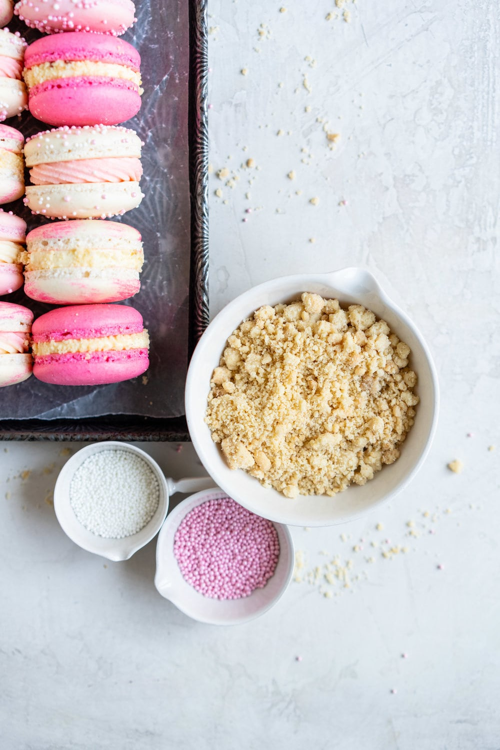 Strawberry shortcake macarons - French Macaron shells are filled with a strawberry filling, cream cheese german buttercream, and finished with a brown butter pie crumb crunch. These encompass summer in every bite. #strawberryshortcake #piecrumb #strawberrymacaron