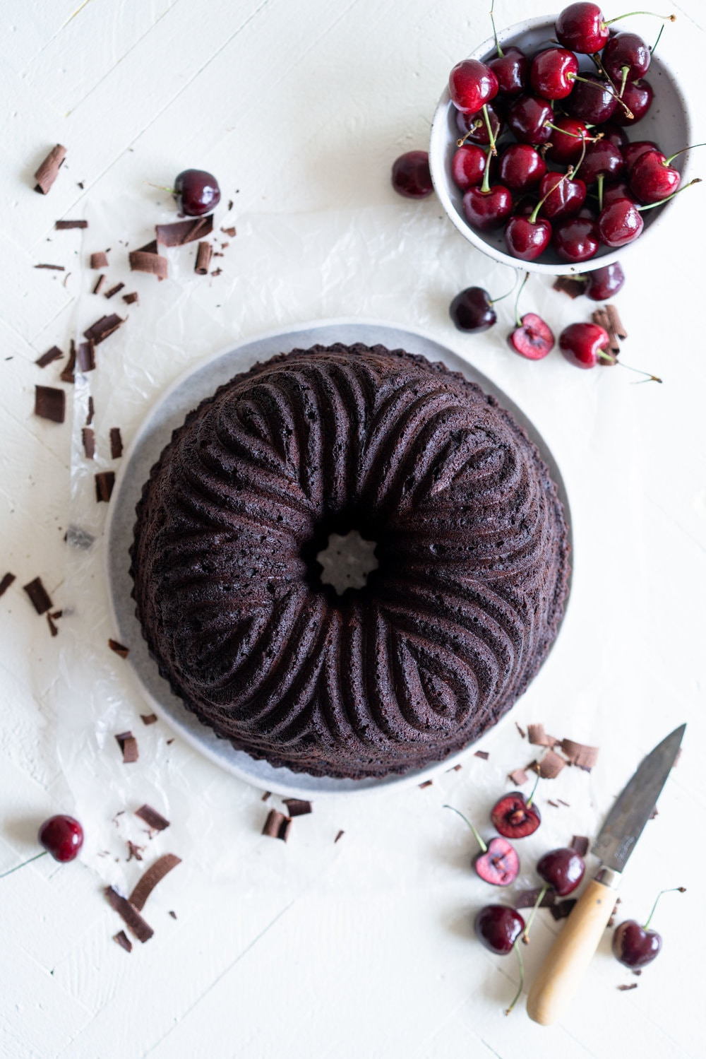 Black forest bundt cake - a rich, tender, chocolate cherry bundt cake that is studded with cherries is topped with fresh softly whipped cream, fresh cherries, and chocolate curls #blackforest #chocolatecherrybundt #chocolatebundtcake