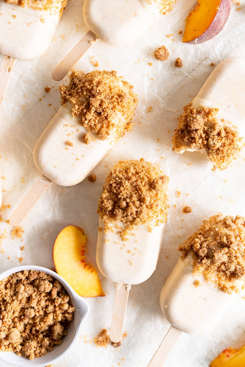 Roasted Peach and Quark Ice Cream Pops with white chocolate dip and brown butter streusel. These are the perfect summer treat - creamy quark, roasted peaches and toasty brown butter streusel.