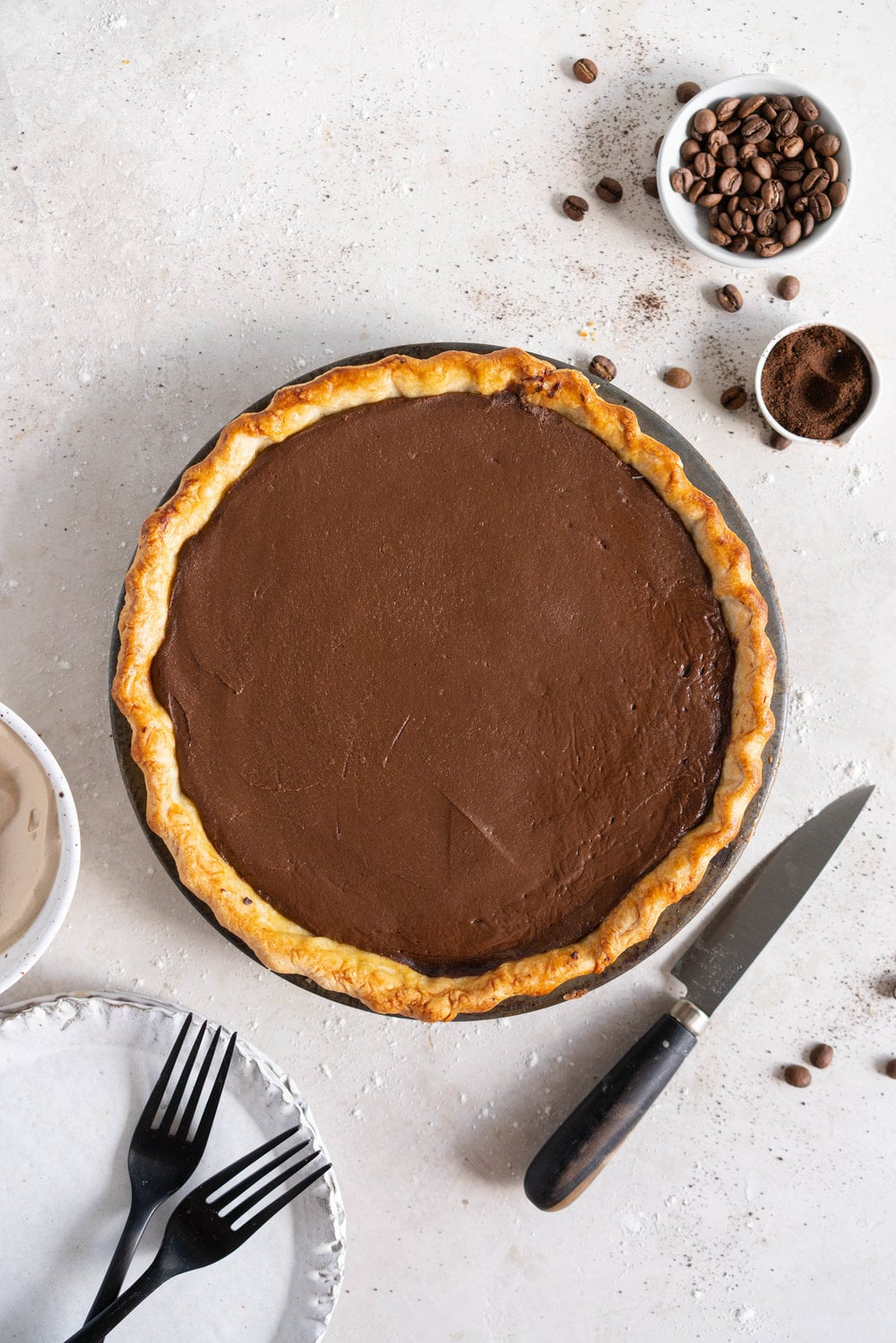 Mocha Cream pie with espresso whipped cream - a crispy blind baked pie crust is filled with a mocha pudding filling and topped with clouds of espresso flavoured whipped cream, before being finished off with coffee beans and espresso powder. This pie is super simple to make and is a coffee lover's dream. #mochapie #creampie #mocha #cloudykitchenpie