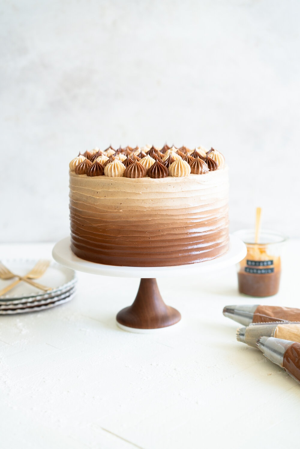 Apple Cider Layer Cake with Spiced Caramel Swiss Meringue Buttercream. This layer cake has reduced apple cider added to the batter, giving it a delicate apple flavour. It is finished with spiced salted caramel swiss meringue buttercream with an ombre finish.  #applecidercake #caramelbuttercream #swissmeringue