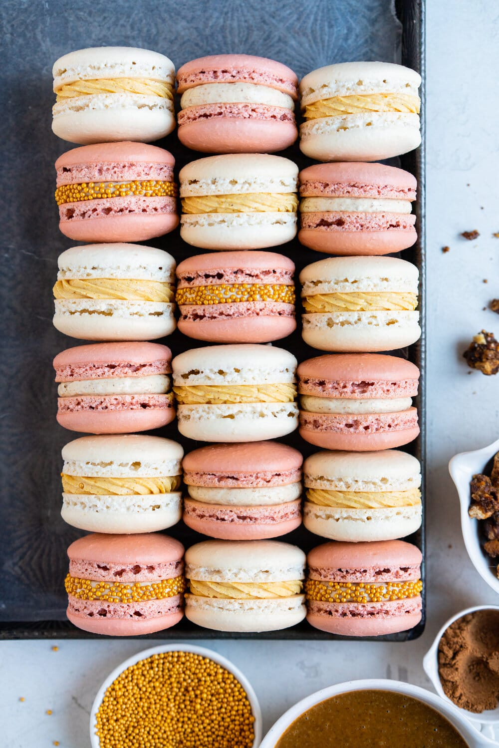 Spiced Pumpkin and Walnut Praline macarons. These are thanksgiving inspired macarons, with a walnut praline swiss meringue buttercream and a spiced pumpkin swiss meringue buttercream, these easy, no-fail french macarons are a perfect addition to your holiday dessert table.