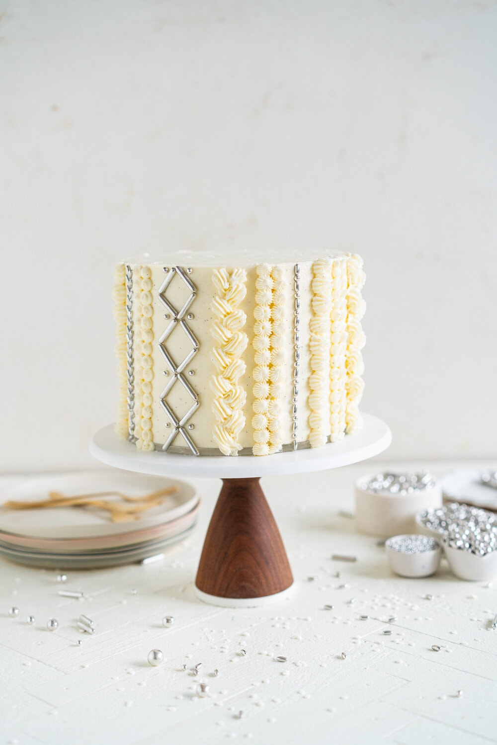 Gingerbread sweater cake - a one bowl soft gingerbread layer cake is stacked with a vanilla bean swiss meringue buttercream, then finished with some sweater inspired piping and silver sprinkles.
