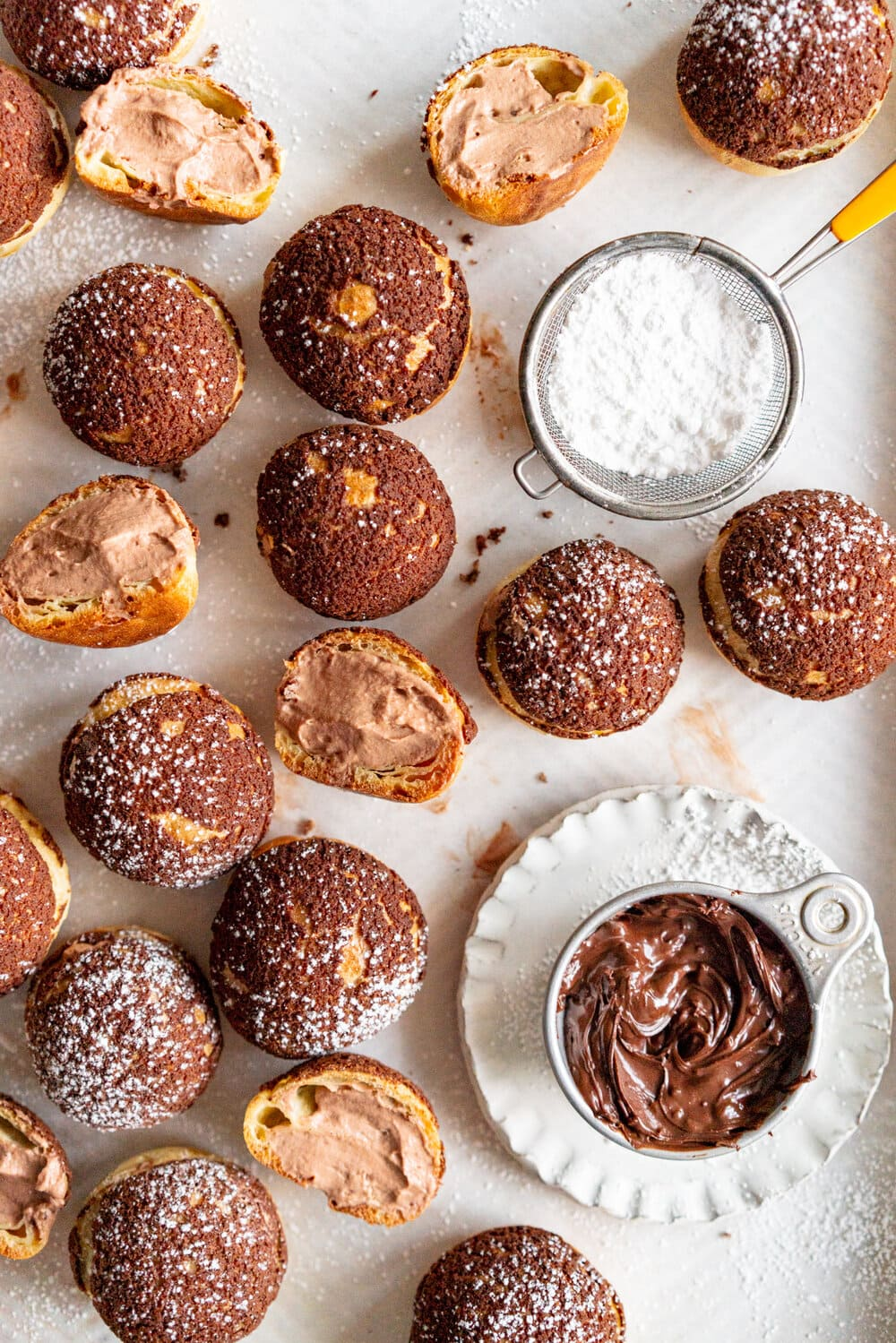 Chocolate Choux au Craquelin with Chocolate Hazelnut Whipped Cream Filling. Rounds of Choux dough are topped with chocolate craquelin and baked to perfection, then filled with silky chocolate hazelnut whipped cream #chouxaucraquelin #creampuffs #chocolatehazelnut