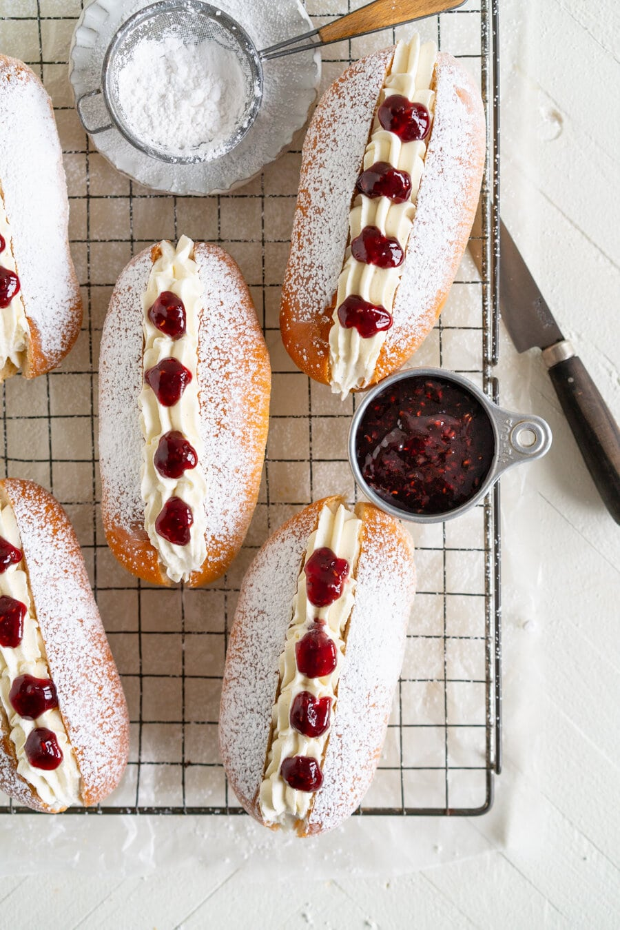 Cream Buns with Vanilla Bean Whipped Cream and Raspberry Jam. A baked version of the New Zealand Classic Bakery jam doughnut. A fluffy soft brioche bun is filled with piped sweetened whipped cream and raspberry jam.