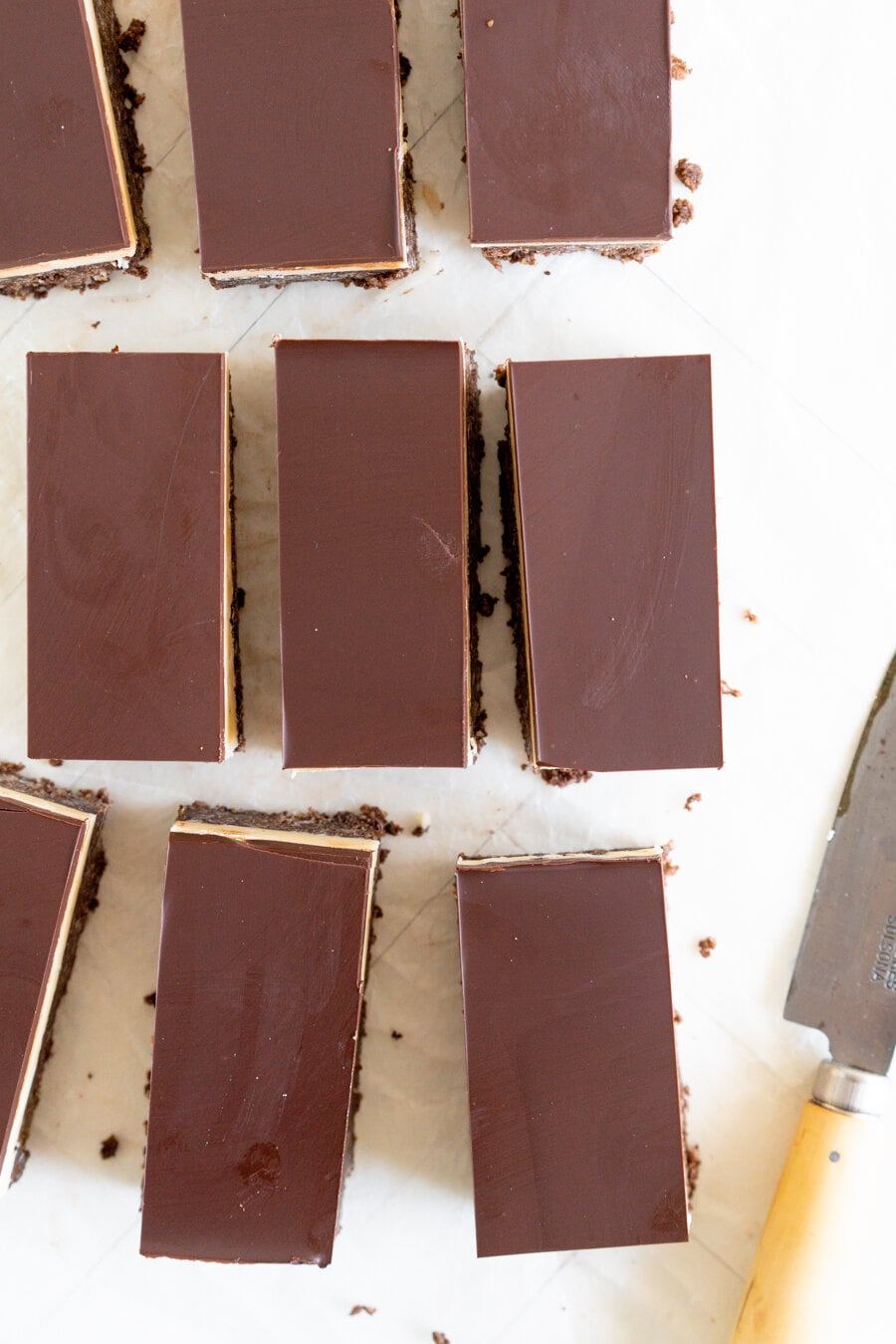 No-Bake Nanaimo Bars - a graham cracker and coconut base is topped with a smooth custard American buttercream and finished off with a super smooth layer of dark chocolate. These are a classic bar, and this no-bake version is so so easy to make!