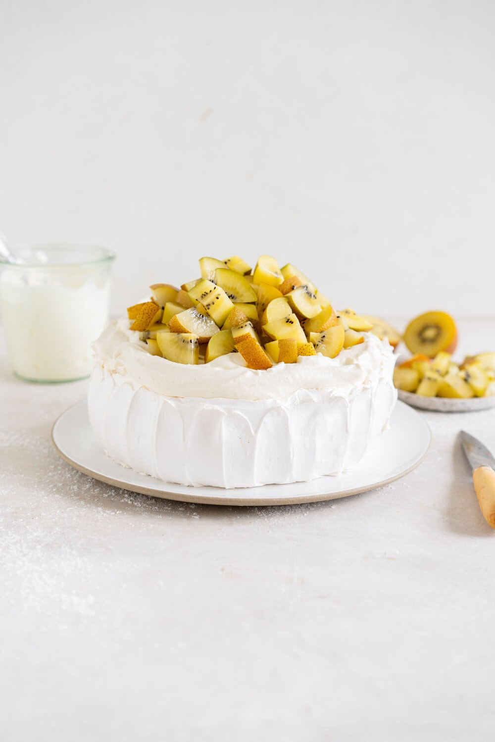 The most perfect, easy pavlova recipe. Using Swiss Meringue instead of the traditional French, this pavlova recipe is crispy on the outside and has a perfect, full, marshmallow center, and is much more stable so is resistant to humidity and changes in weather. It is easy to make and the perfect crowd pleaser. This is the most perfect year round dessert. Topped with Manuka Honey whipped cream and golden kiwifruit, this is a New Zealand classic.