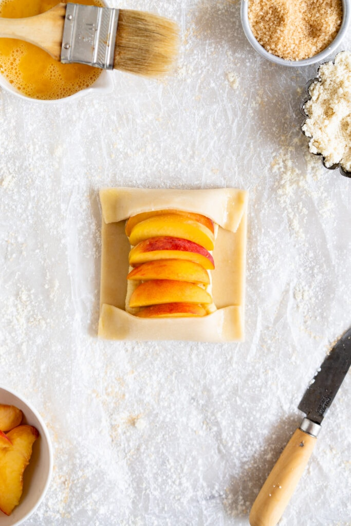 Peach Galette during assembly with edges folded over peaches