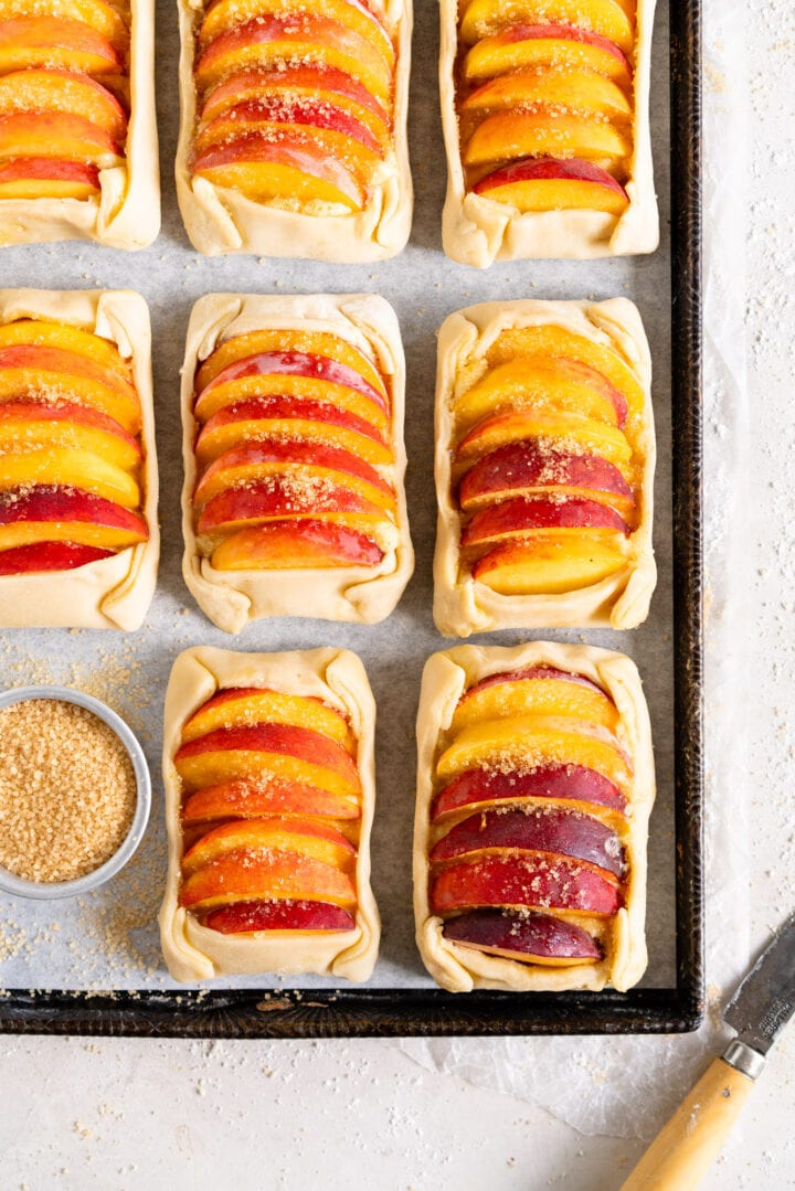 Side image of peach galettes on a sheet pan