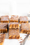 side on shot of ginger caramel slice showing the cut shot and drizzled chocolate