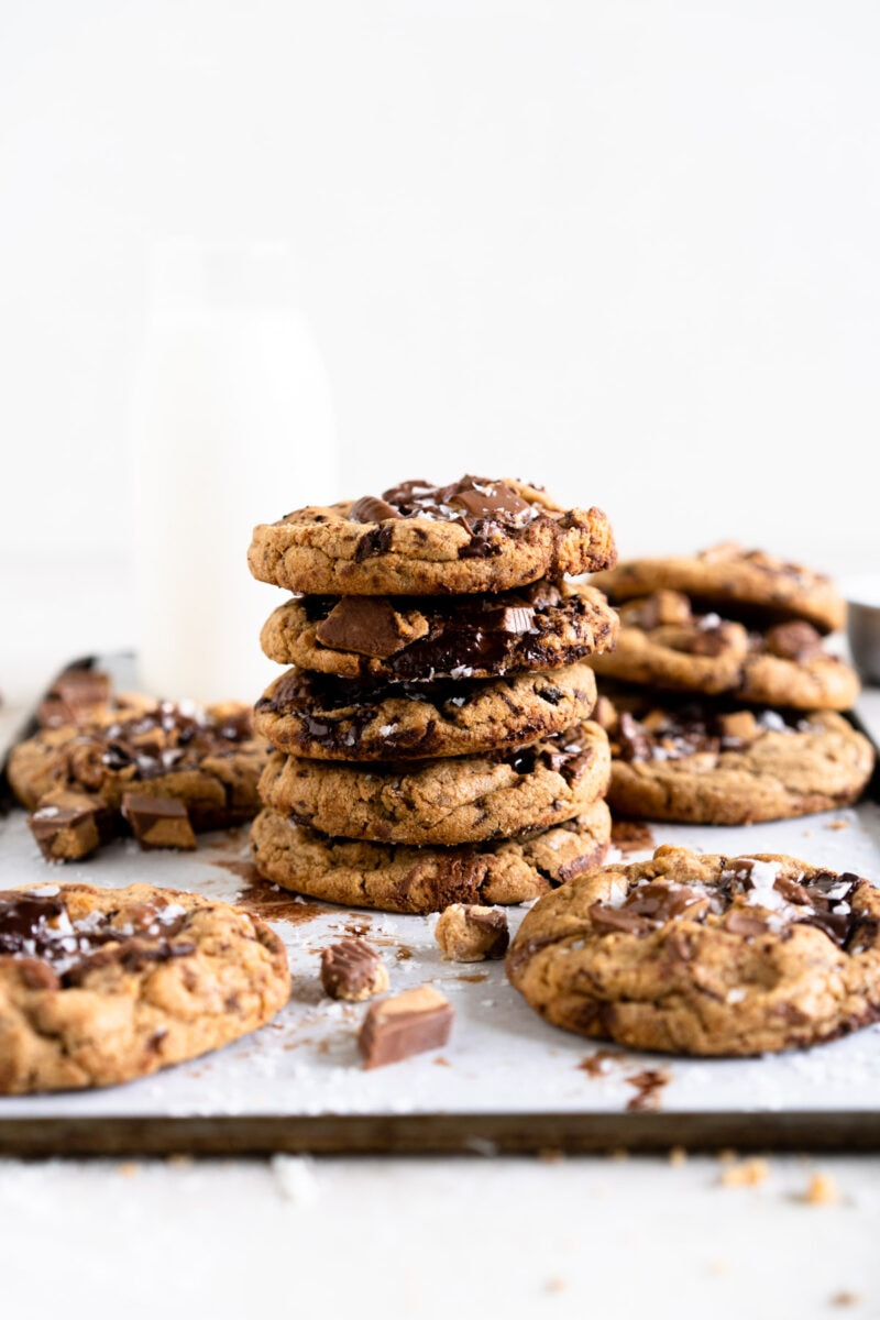 Stacked up chocolate chip cookies with extra cookies in the foreground and a bottle of milk in the background