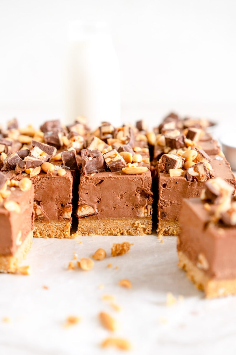 Chocolate Snickers Cheesecake topped with Snickers bar and Chopped Peanuts
