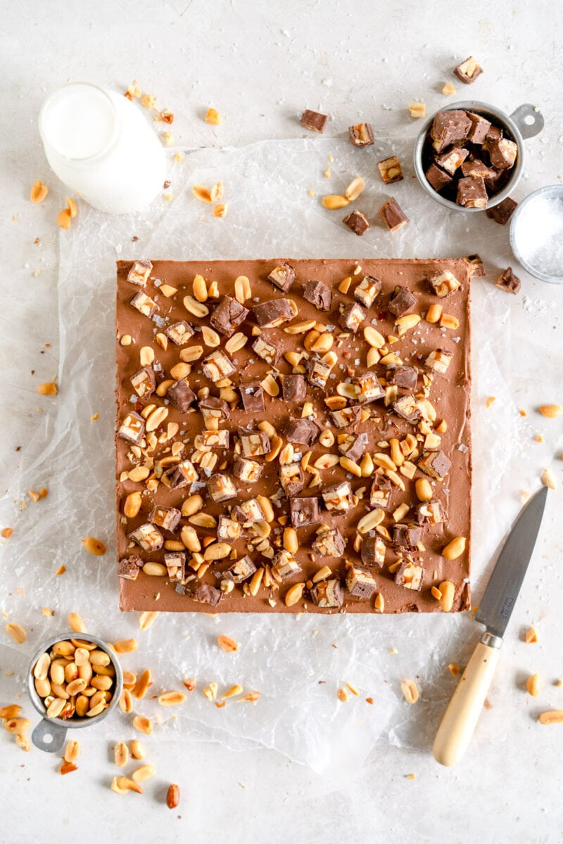 Top Down shot of chocolate cheesecake with peanuts and snickers